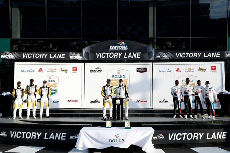 The drivers celebrate their GTLM victory on a socially-distanced victory platform.