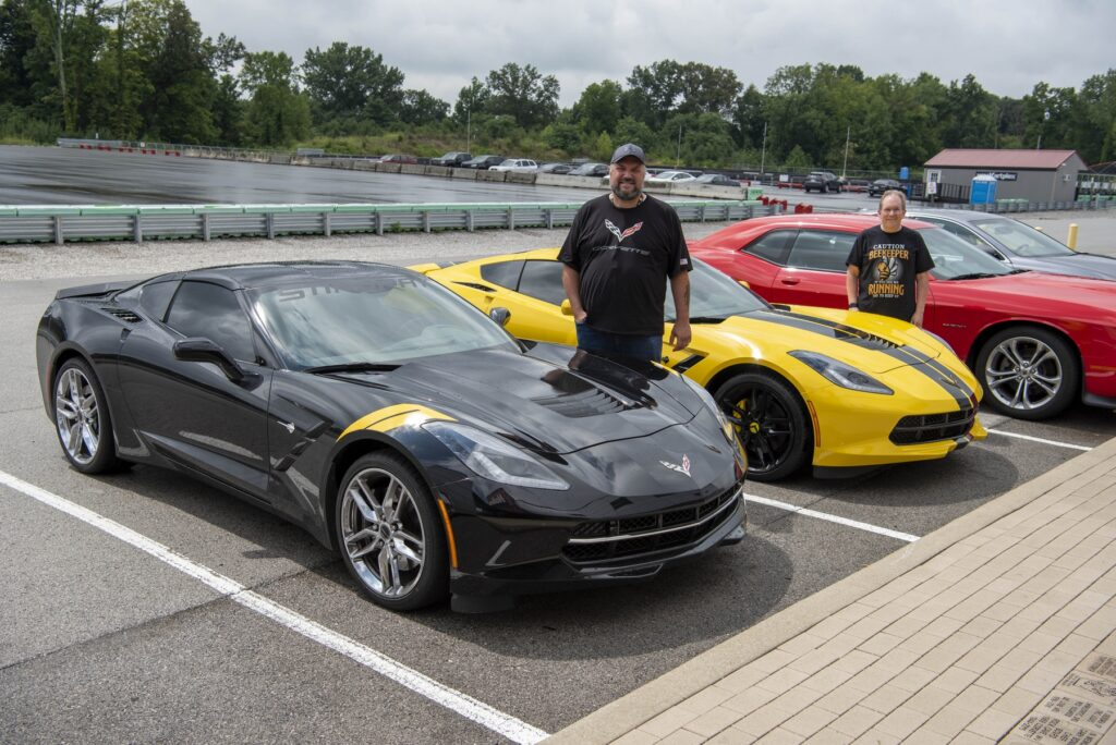 Scott (left) and Cliff with their C7 Stingrays at the NCM Motorsports Park track.