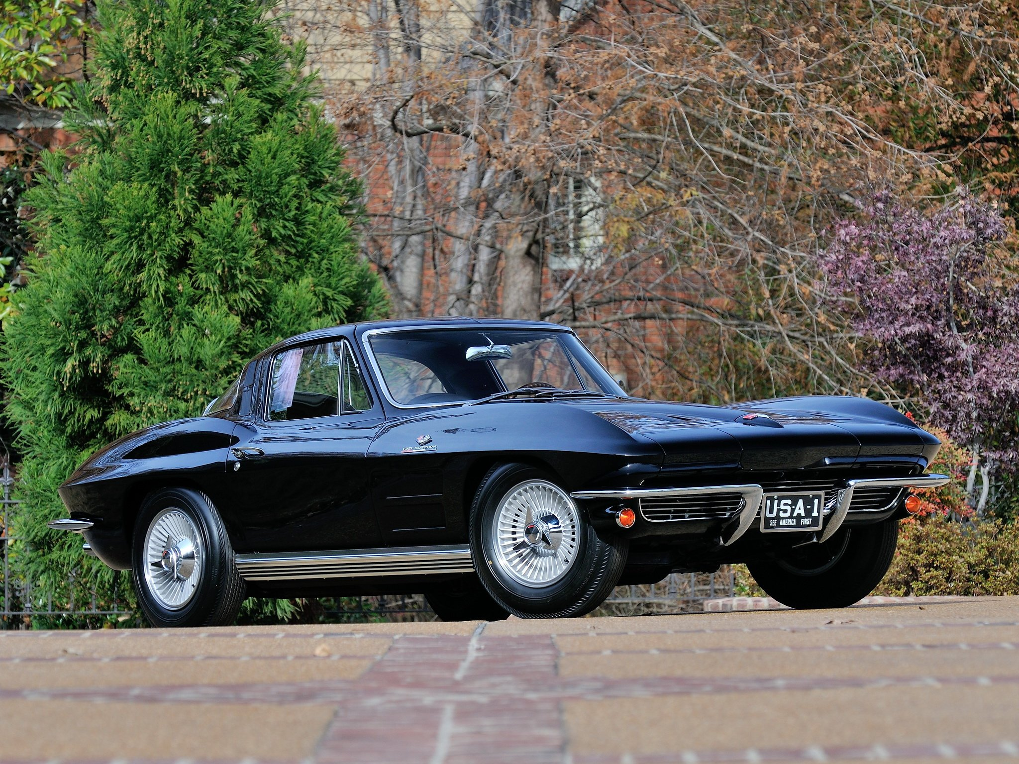 Black 1964 L84 Stingray Corvette on road with trees in background