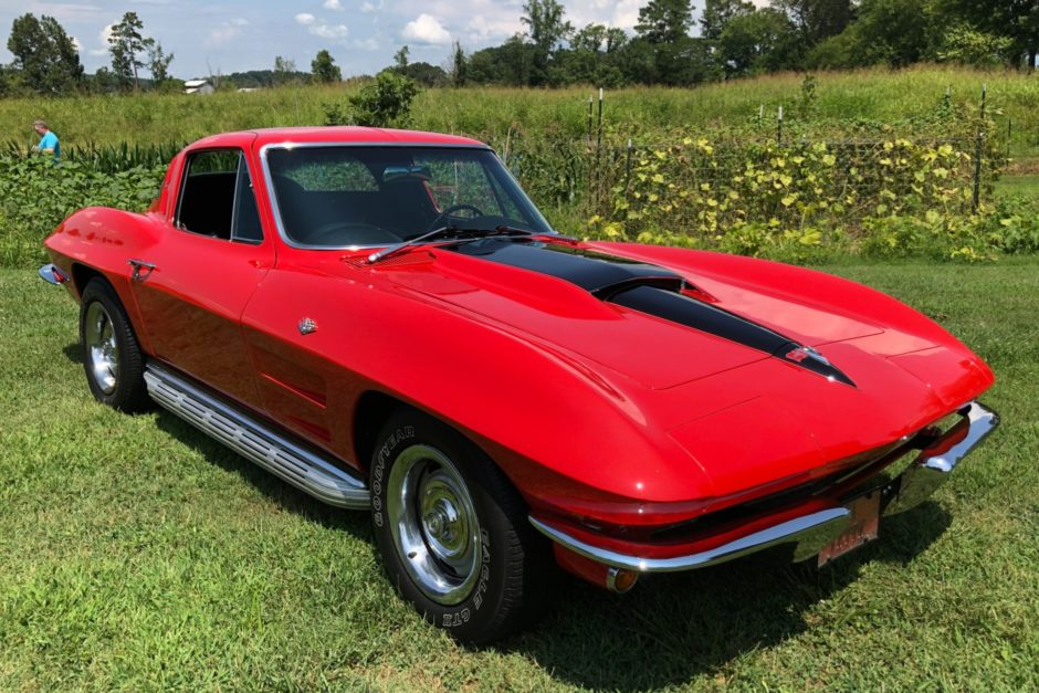 Red 1964 Corvette with L76 engine sitting in field