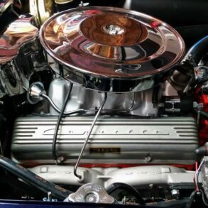 Exposed 1964 L76 engine sitting in blue Corvette with hood open