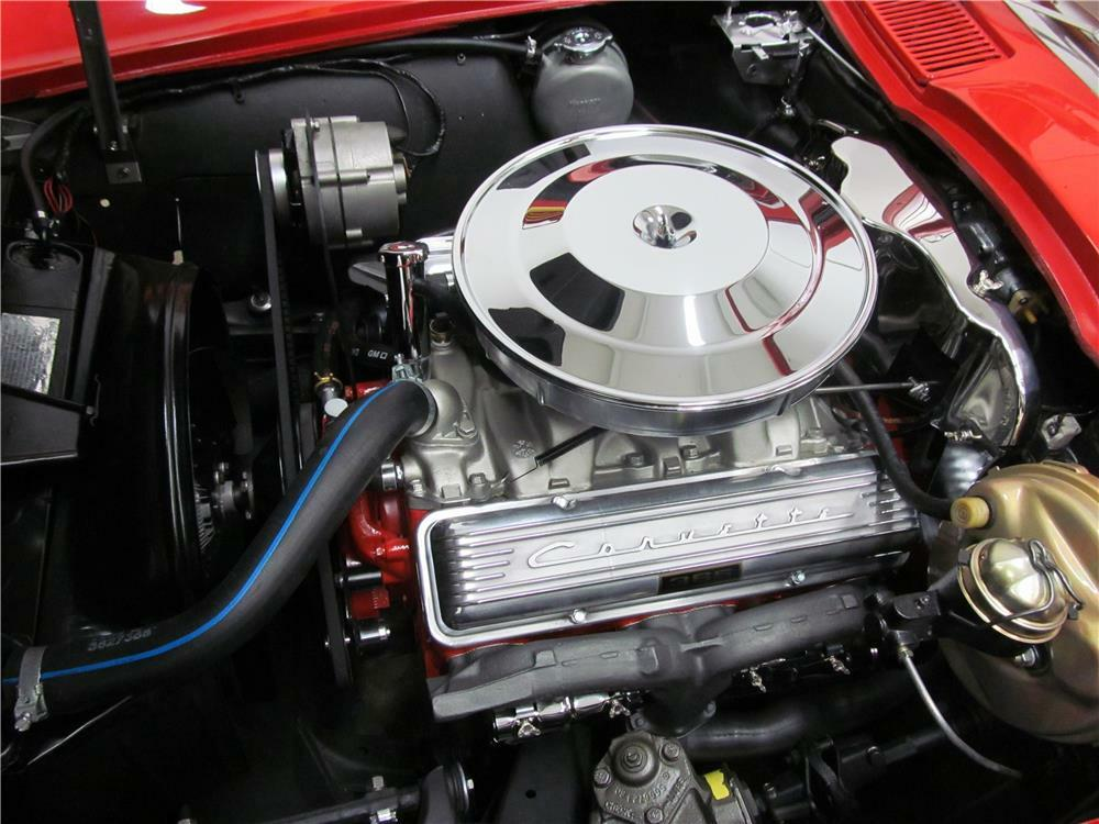 Close-up of 1964 L76 engine sitting in open hood of red Corvette