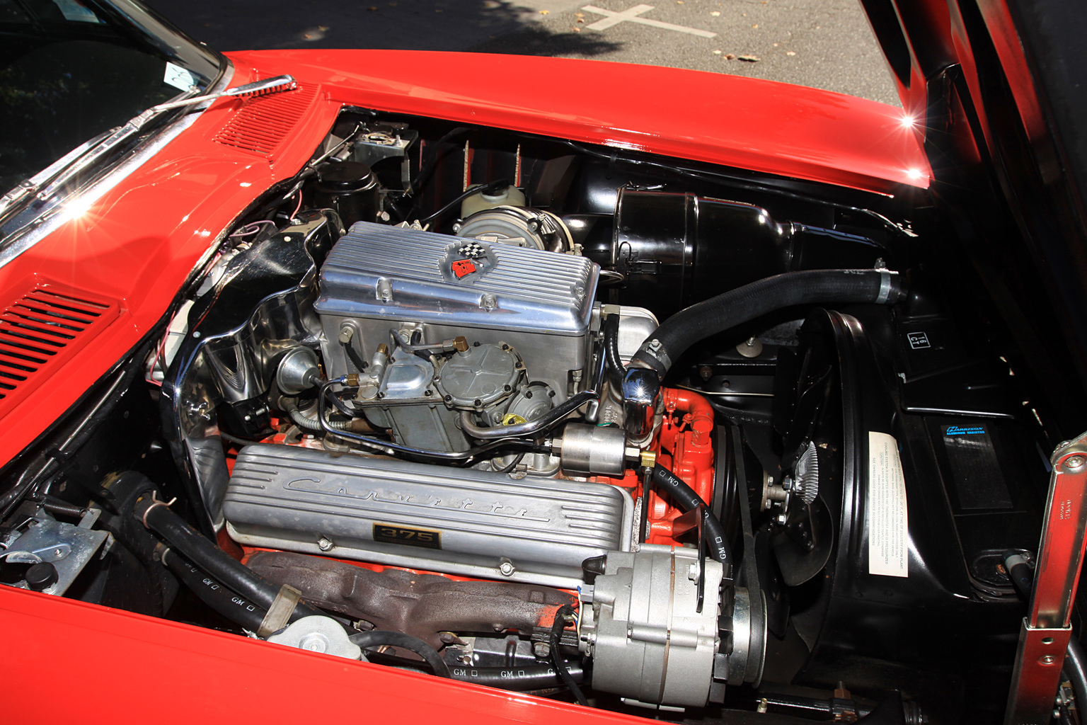 Exposed 1964 L84 engine sitting in red Corvette with hood up